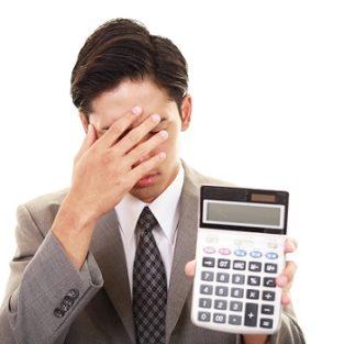 計算機を持つ疲れた表情のビジネスマン
