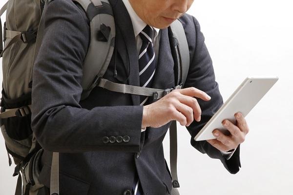 ザックを背負いタブレット端末で検索するビジネスマン