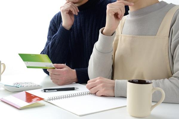 模造品の通帳を確かめながら家計を話し合う夫婦