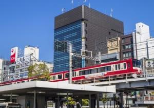 「川崎」駅東口の高架線路を走る京浜急行線の赤い車両