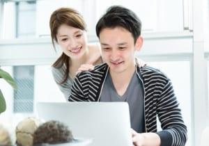 男性のパソコン作業を眺める女性